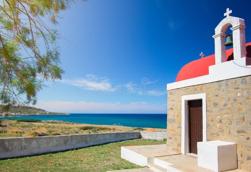 Fantastisk bildmässig sikt av en gammal stenkyrka bredvid det blåa havet, Milatos, Kreta royaltyfria foton
