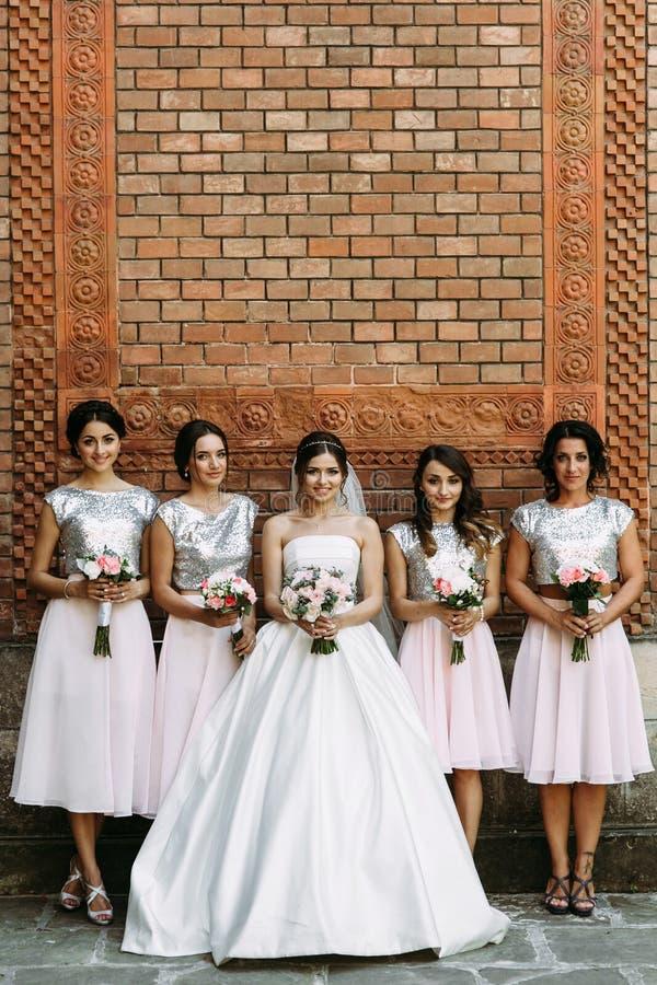 Fantastisk brud i den brud- klänningen med brudtärnorna arkivfoto