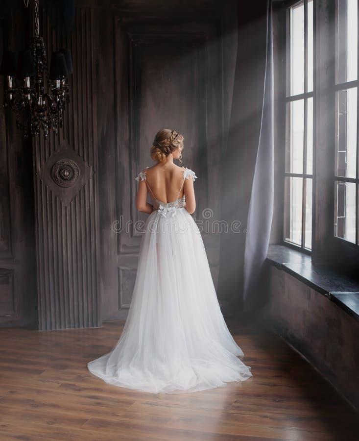 Fantastisk dam i lång vit förtjusande dyr ljus klänning med drevet och öppna tillbaka ställningar med baksida till kameran, flick fotografering för bildbyråer