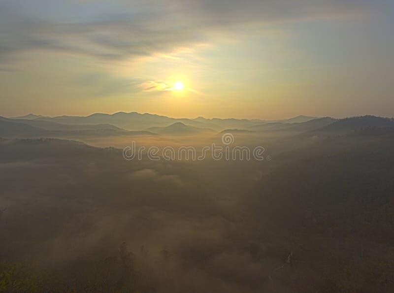 Fantastisk drömlik soluppgång överst av det steniga berget med sikt in i den dimmiga dalen Berg beskådar dimmigt berg Drömlik mes royaltyfri fotografi