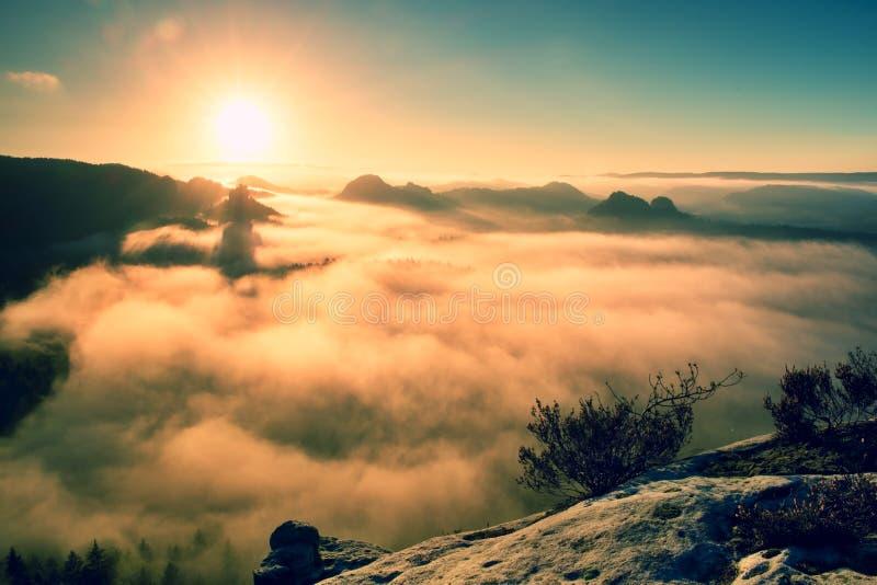 Fantastisk drömlik soluppgång på överkanten av det steniga berget med sikten in i den dimmiga dalen arkivbilder