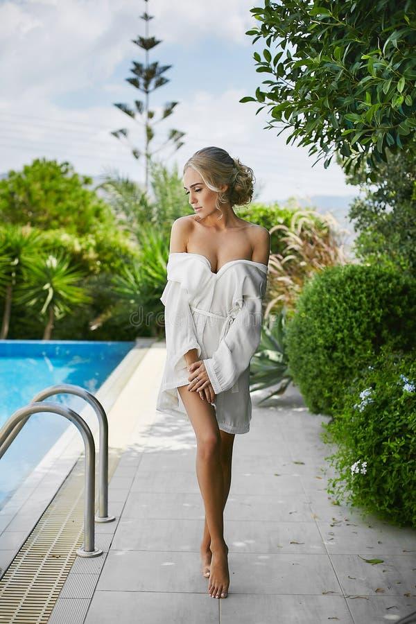 Fantastisk förförisk skönhet, den sexiga blonda barnmodellkvinnan med den perfekta halva-nakna kroppen endast i peignoir ser ner  royaltyfria bilder