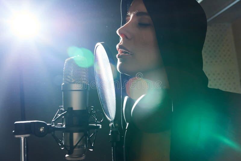 Fantastisk flicka som sjunger i tänd baksida royaltyfri foto