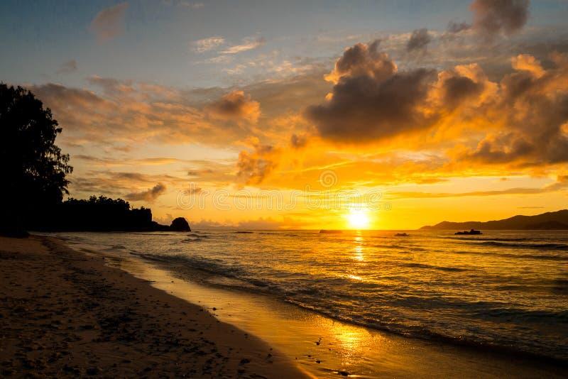 Fantastisk guld- solnedgång med enorma moln i en tropisk ö, Anse royaltyfri foto