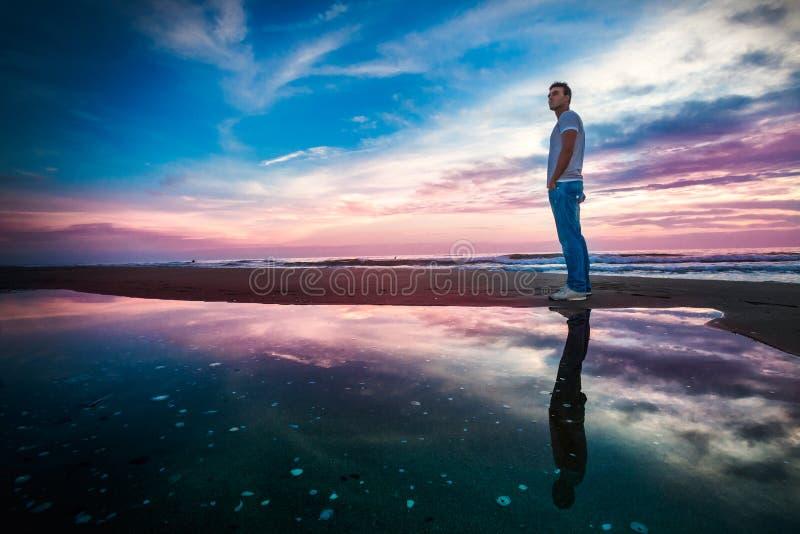 Fantastisk havssolnedgång med reflexion Enslig man arkivfoto