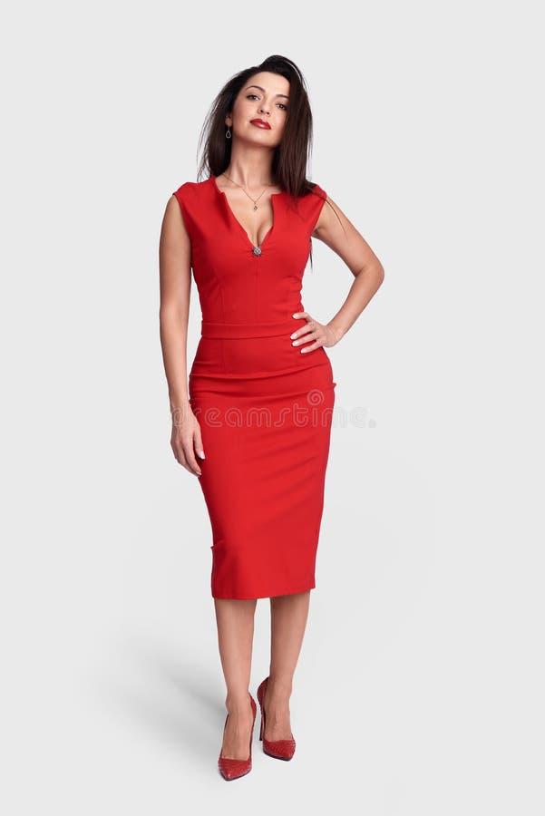 Fantastisk kvinna i stilfull röd klänning royaltyfri bild