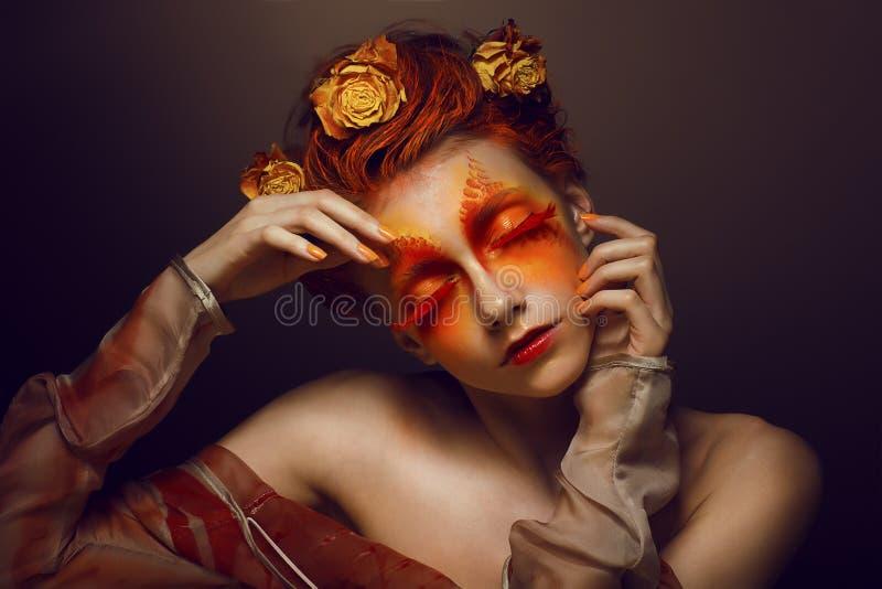 Bodyart. Fantasi. Konstnärlig kvinna med rött - guld- Makeup och blommor. Färga royaltyfri fotografi