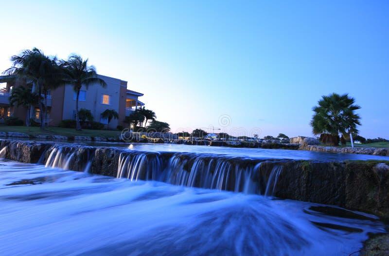 Fantastisk nattlandskapsikt Rinnande vatten och att bygga med tända fönster och gröna växter på bakgrund för blå himmel Aruba ö n royaltyfria foton