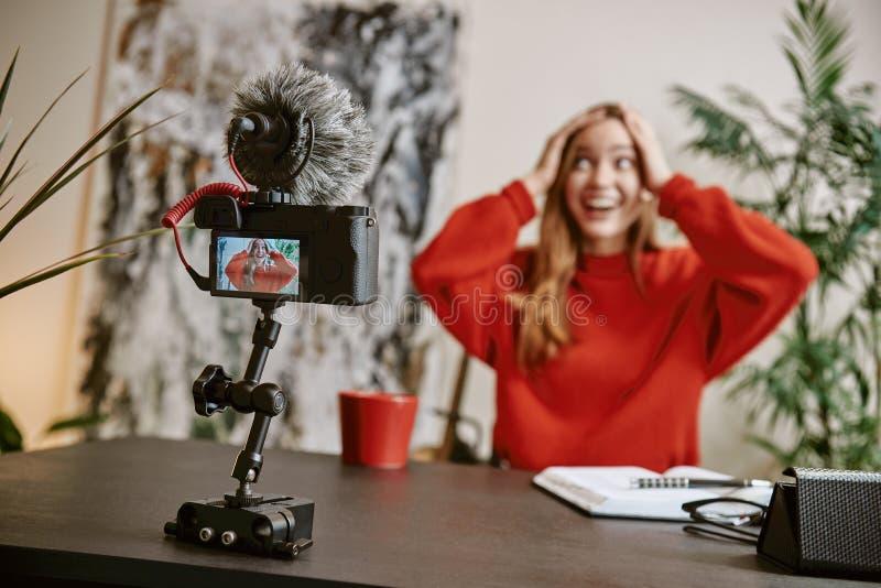 Fantastisk nyheterna! Den förvånade kvinnliga bloggeren trycker på ett huvud och ler medan den levande TV-sändning för hennes vlo royaltyfria bilder
