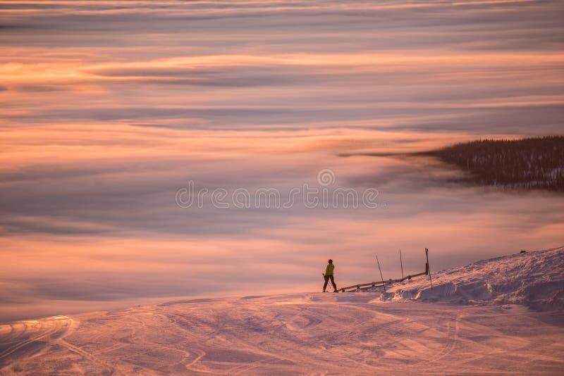 Fantastisk rosa himmel och berg lite varstans Vänner som har gyckel överst av berget, medan skida/snowboarding Hisnande solnedgån royaltyfria foton