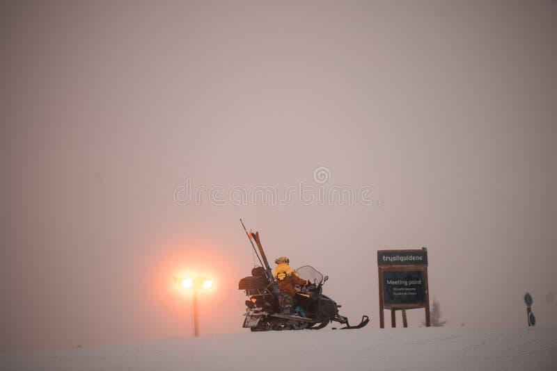 Fantastisk rosa himmel och berg lite varstans Vänner som har gyckel överst av berget, medan skida/snowboarding Hisnande solnedgån arkivfoto