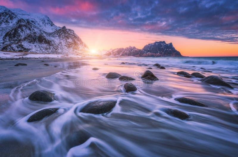 Fantastisk sandig strand med stenar i suddigt vatten på solnedgången royaltyfria bilder