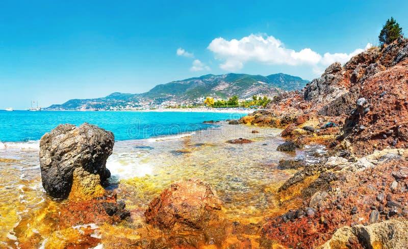 Fantastisk sikt på den steniga tropiska stranden på solig sommardag i Alanya, Turkiet Turkisk seascape med berg och vaggar royaltyfria foton