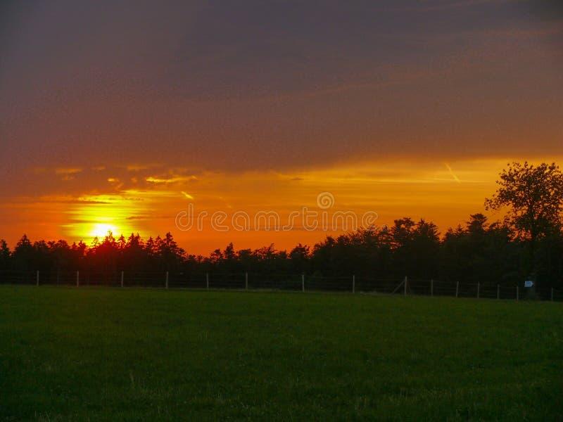 Fantastisk solnedgång över ett mörker - det gröna bygdlandskapet av Rolling Hills med solen strålar genomträngande himmel och bel royaltyfri fotografi