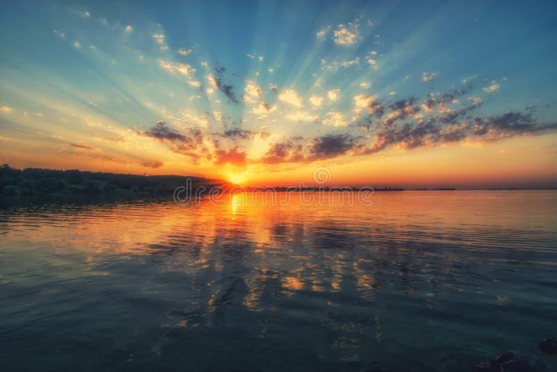 Fantastisk solnedgång över floden Härliga moln, pittoreska solstrålar och färgrik reflexion i vattnet arkivbild