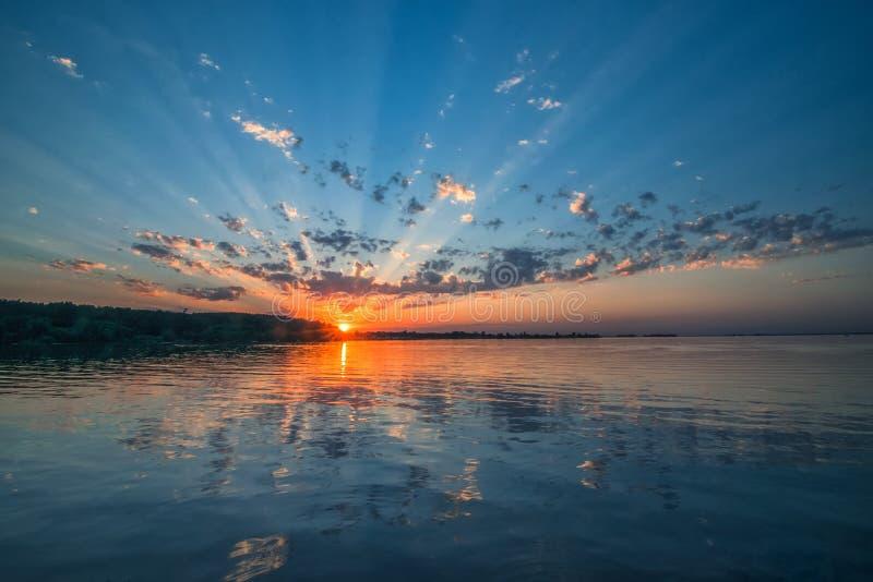 Fantastisk solnedgång över floden Härliga moln, pittoreska solstrålar och färgrik reflexion i vattnet arkivbilder