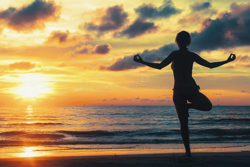 Fantastisk solnedgång för yogakvinnakontur på havsstranden relax royaltyfria bilder