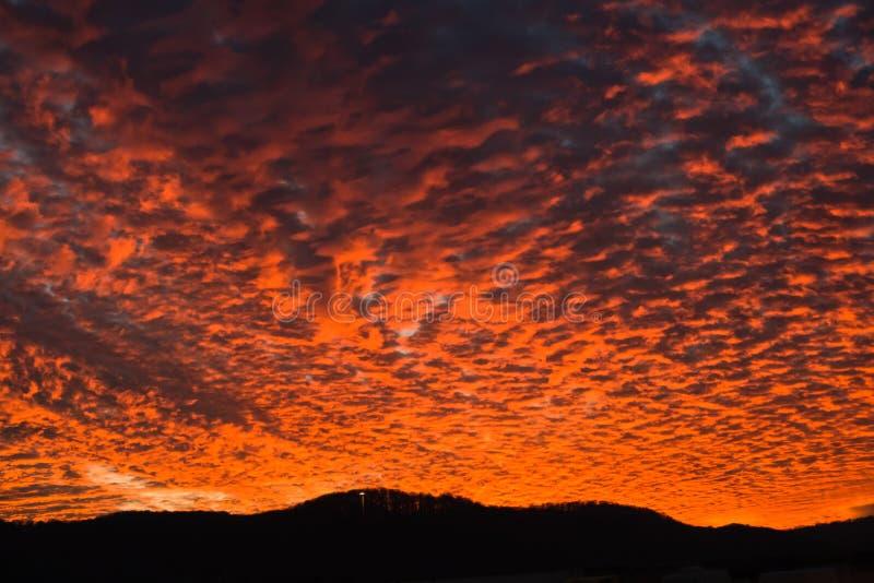Fantastisk solnedgång med stor orange brand i himlen på en väg royaltyfria foton