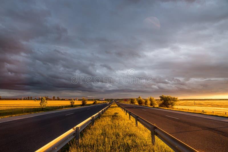 Fantastisk solnedgång på huvudvägen royaltyfri bild