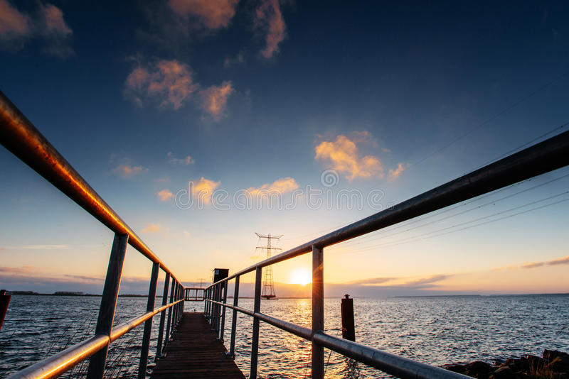 Fantastisk solnedgång som exponerar den långa pir på sjön royaltyfri bild