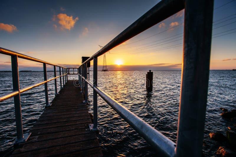 Fantastisk solnedgång som exponerar den långa pir på sjön royaltyfri fotografi