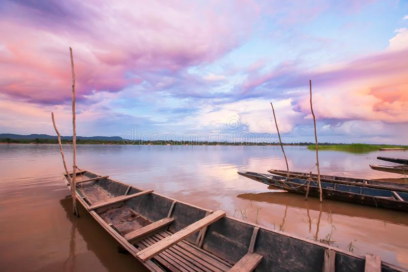 Fantastisk solnedgånghimmel över Mekonget River Färgrika moln som reflekterar på ett vatten, traditionella thai fiskebåtför arkivbild