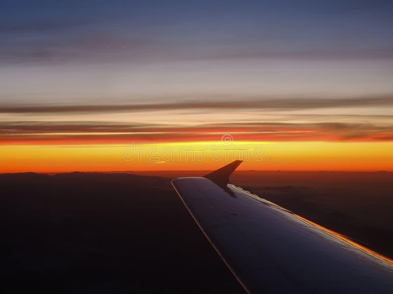 Fantastisk soluppgång över fjällängarna som tas från flygplanfönstret arkivfoton