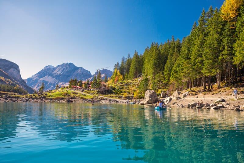Fantastisk tourquise Oeschinnensee med vattenfall, trächalet och schweiziska fjällängar, Berner Oberland, Schweiz royaltyfri bild