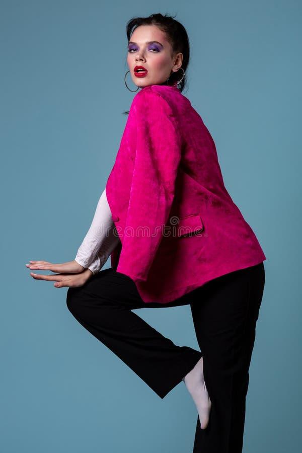 Fantastisk ung brunettkvinna i det moderiktiga rosa omslaget som står på ett ben arkivfoto