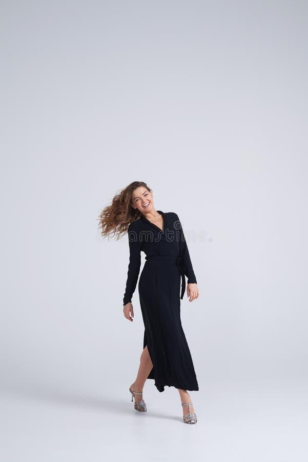 Fantastisk ung stilfull kvinna i den svarta klänningen som poserar på kameran royaltyfria bilder