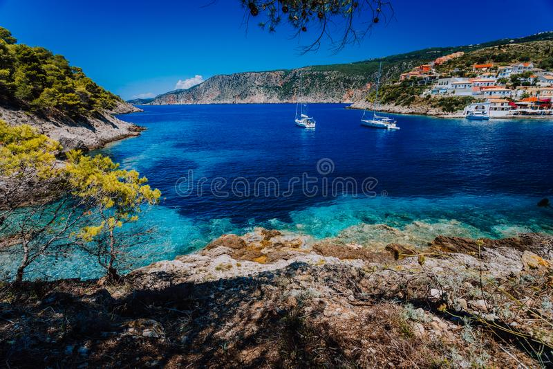 Fantastiska Grekland, vit seglar fartyg i blå fjärd av den pittoreska färgrika byn Assos i Kefalonia royaltyfri bild