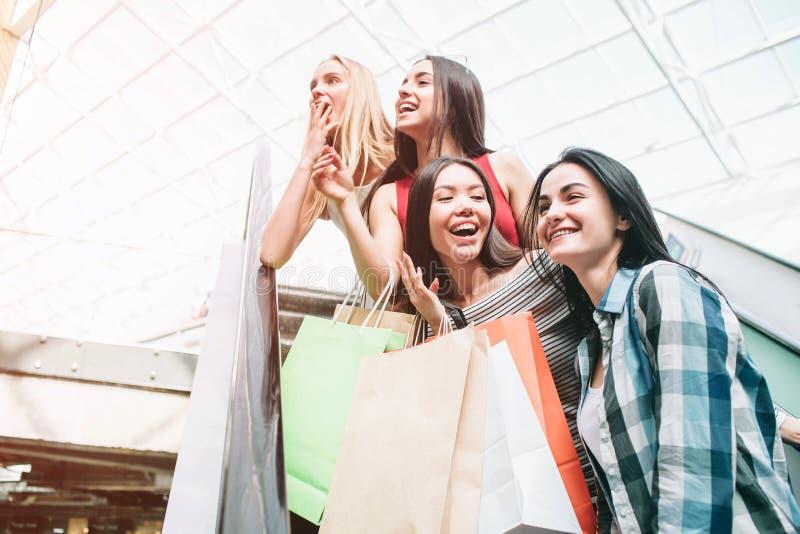 Fantastiska och attraktiva damer står på rulltrappan De ser till det vänstert De ler Också tonåringar arkivfoton