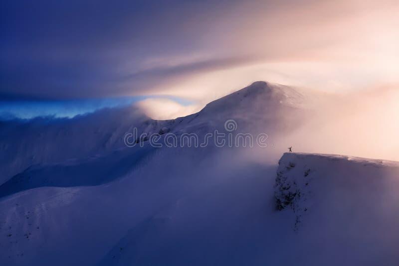 Fantastiskt landskap med en fri ryttare och en bergsbestigare, höga berg i snö och dimman med att intressera färg royaltyfri bild