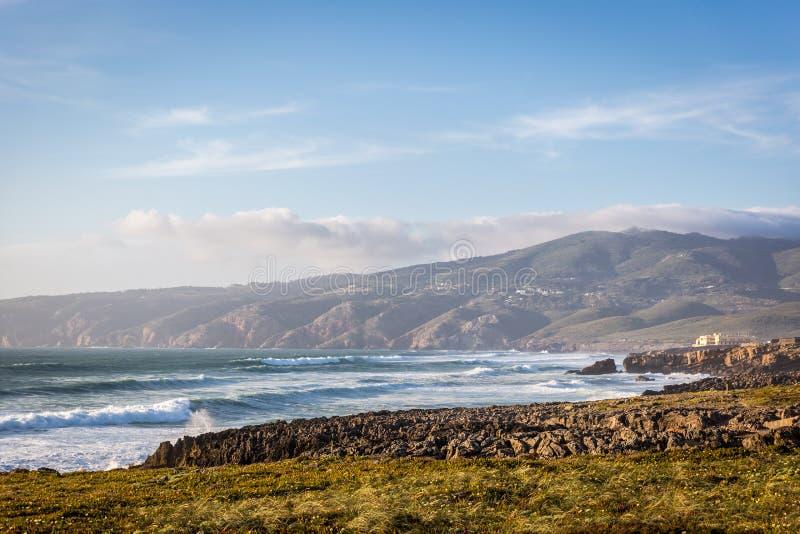 Fantastiskt landskapscenario på den Guincho stranden i Cascais, Portugal Solnedgångfärger, berg, stora vågor arkivfoto