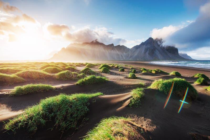 Fantastiskt västra av bergen och de vulkaniska lavasanddyerna på stranden Stokksness, Island Färgrik sommarmorgon royaltyfri bild