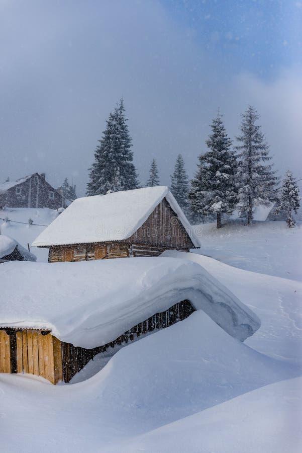 Fantastiskt vinterlandskap med trähuset i snöig berg arkivbild