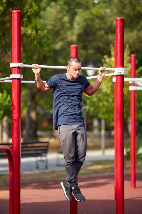 Fantastyczny młody człowiek robi Ups na crossbars na zamazanym tle Siły pojęcie zdjęcia stock