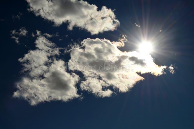 Fantastyczny oświetleniowy skutek białe puszyste chmury z słońce promieniami w niebieskim niebie obrazy royalty free