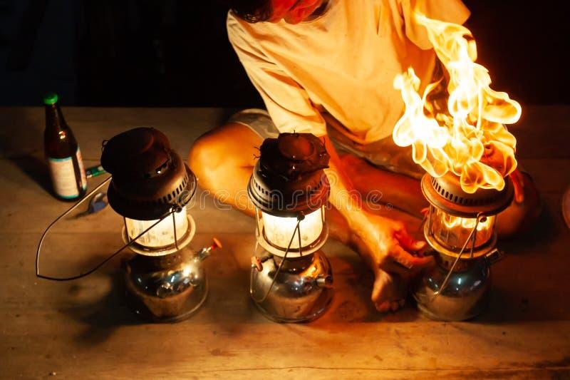 Fantastyczny ogień płonie przy nocą stary człowiek z trzy rocznik nafty naciska lampionami na drewnianym, piękny jaskrawy palić zdjęcia stock