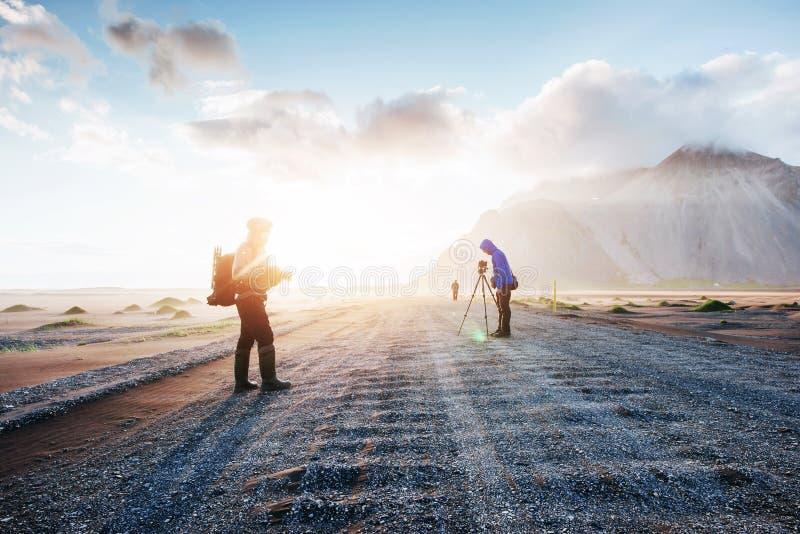 Fantastyczny za zachód od powulkanicznych lawowych piasek diun i gór plażowy Stokksness Turyści podróżuje przez obraz stock