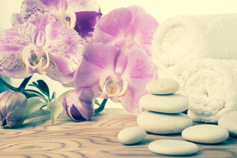 Fantastyczny zdroju wciąż życie z kamieniem, lilą orchideą i ręcznikiem, zdjęcie stock