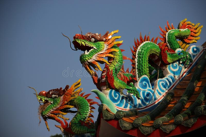Multicolor Ceramic Dragons With Blue Sky Background. Still life Moses Dragons colorful fantasy animals decoration on shrine roof in Khonkaen Thailand stock photography