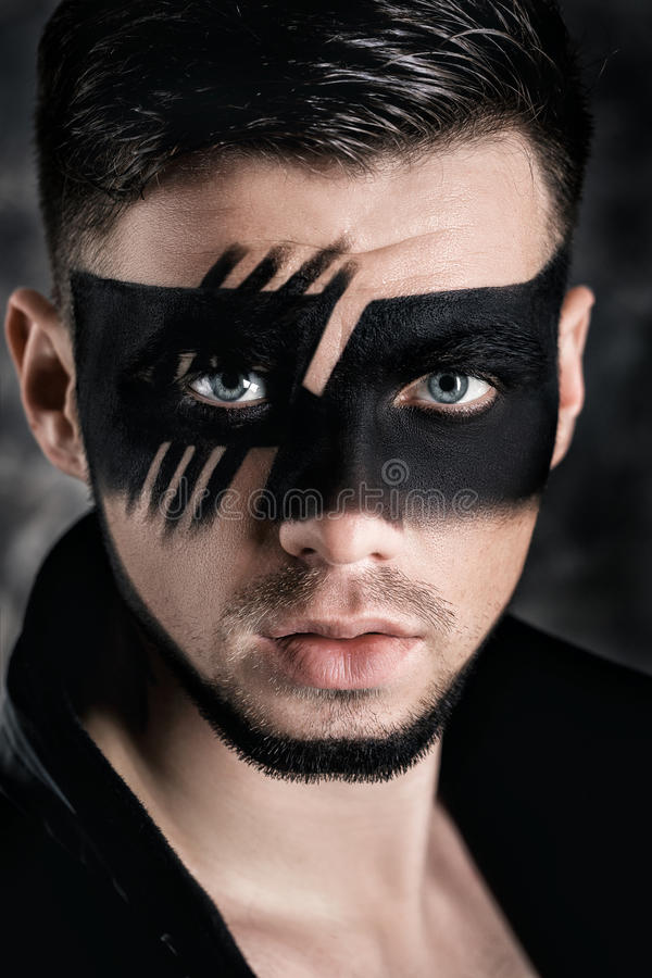Fantasy art makeup. man with black painted mask on face. Close up Portrait. Professional Fashion Makeup. Fantasy art makeup. Young man with black painted mask royalty free stock photography