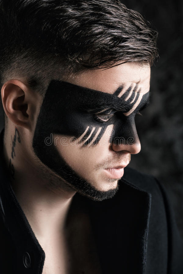 Fantasy art makeup. man with black painted mask on face. Close up Portrait. Professional Fashion Makeup. Fantasy art makeup. Young man with black painted mask stock images