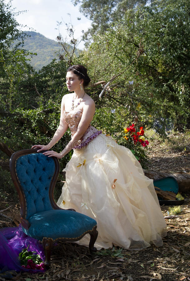 Fantasy bride in golden dress posing in forest. Fantasy bride wearing a strapless golden wedding dress, tiara and gold jewelry, posing in the sunlight in an royalty free stock photography