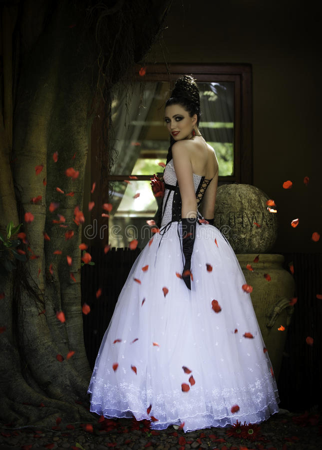 Fantasy bride surrounded by red rose petals stock photos