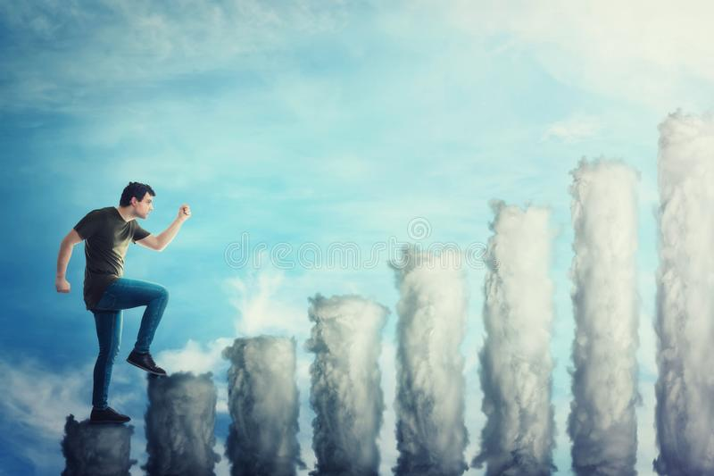 Fantasy concept as a confident guy stepping on a staircase as a graph made of clouds. Man going up hurried over a blue sky stock photo