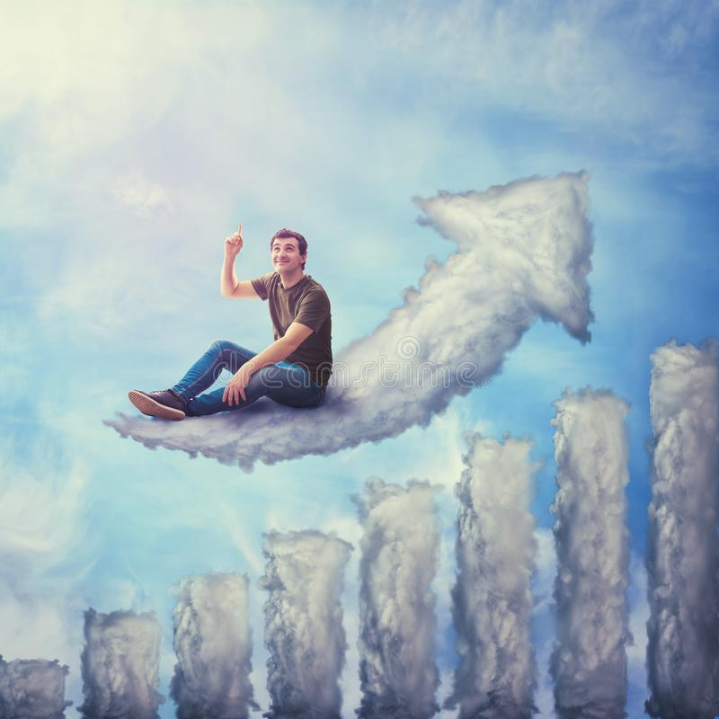 Fantasy concept as an excited guy seated on a cloud shaped as increasing graph, looking and pointing index finger up, dreaming of stock image