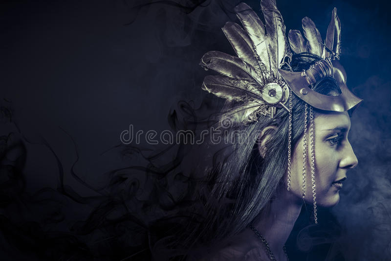 Fantasy concept, woman with fashioned golden mask. Valkyrie, Golden statue concept. Arty portrait of model with golden mask and shiny lashes. Perfect sporty body stock photo