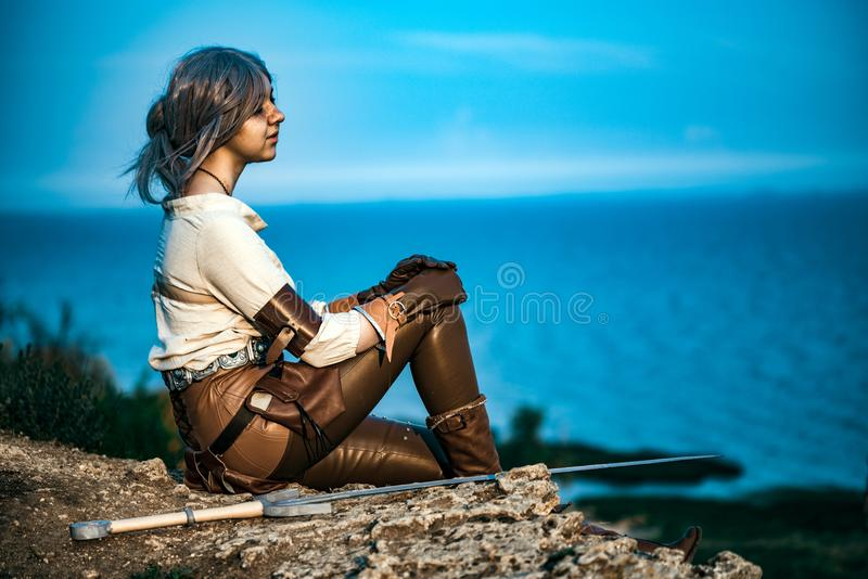 Fantasy cosplay beautiful Witcher girl on cliff stock image